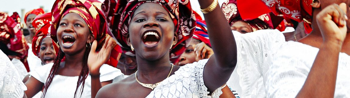 Worshippers dressed in white, singing and raising hands