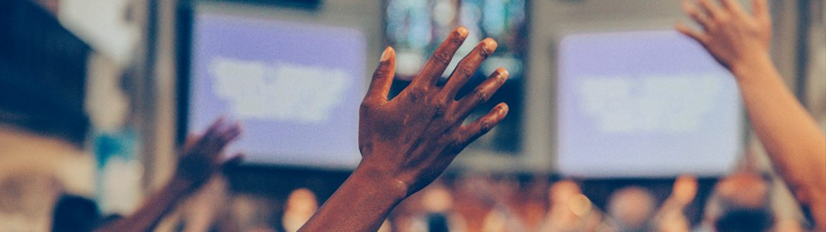 Hands raised in worship with song lyrics projected on screens in the background